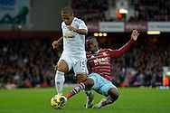 Enner Valencia of West Ham United tackles Wayne Routledge of Swansea City. Barclays Premier league match, West Ham Utd v Swansea city at the Boleyn ground, Upton Park in London on Sunday 7th December 2014.<br /> pic by John Patrick Fletcher, Andrew Orchard sports photography.
