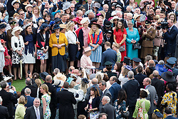 Queen Elizabeth II (centre) greets guests at a garden party at Buckingham Palace in London.