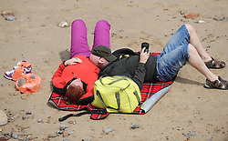 © Licensed to London News Pictures. 27/05/2013..Saltburn, England..A couple relax on the beach as they enjoy the warm bank holiday weather at Saltburn by the Sea in Cleveland....Photo credit : Ian Forsyth/LNP