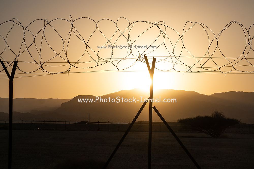 Open Border Barbed wire fence at sunset