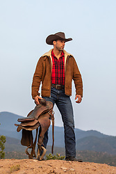 rugged cowboy with a saddle on a mountain top