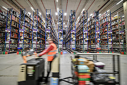 Embargoed to 0001 Friday November 16 A worker on a motorised trolley passes thousands of items on high level racking at Amazon's fulfillment centre in Swansea, in the run up to Black Friday.
