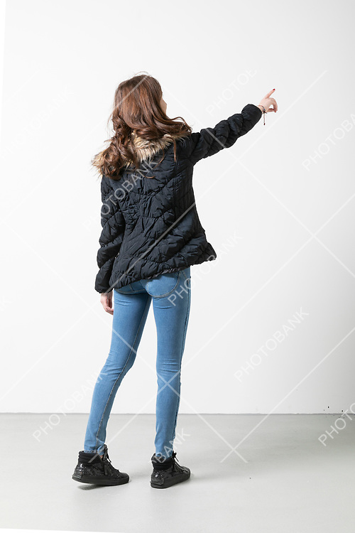 Girl with long hair seen from behind indicates an imaginary point. White background