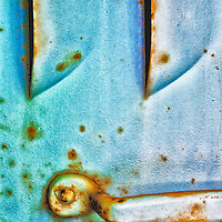 Metallic finish on antique truck blended with layers of rust.