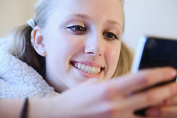 Teenage girl using smart phone on couch, smiling