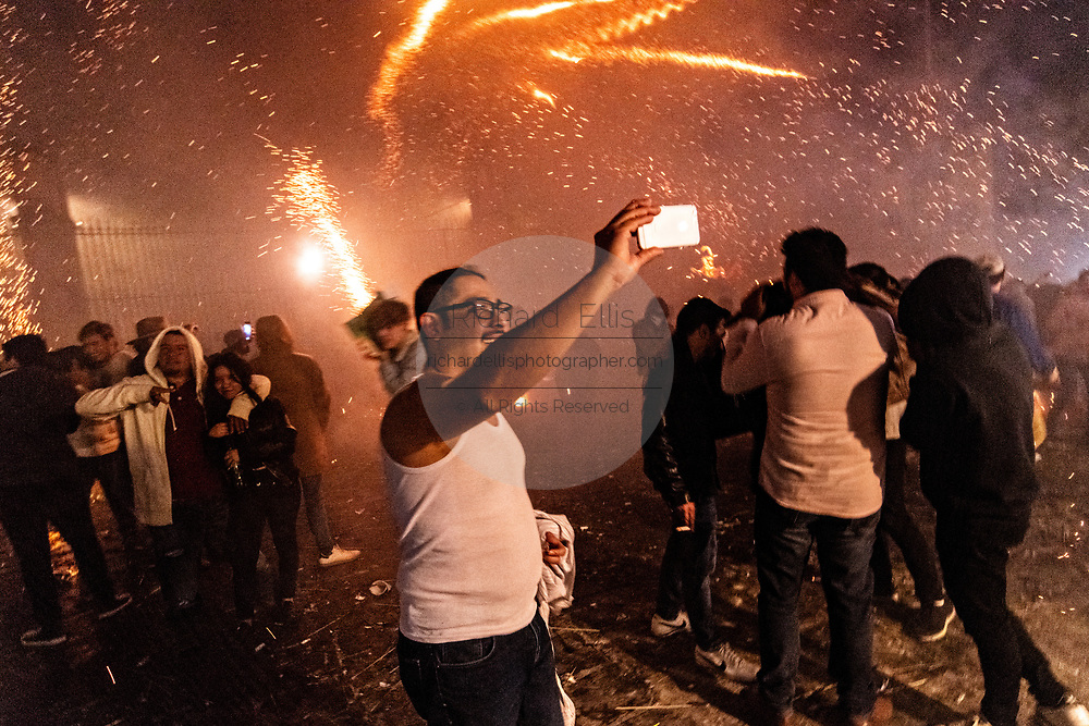 A celebrant takes a selfie as dozens of sky rockets rain down in the chaos of the Alborada festival in front of the Parroquia San Miguel Archangel church September 29, 2018 in San Miguel de Allende, Mexico. The unusual festival celebrates the cities patron saint with a two hour-long firework battle at 4am representing the struggle between Saint Michael and Lucifer.