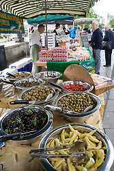 Fresh produce on a stall at an outdoor Farmer's market; customer and stallholder in the background,