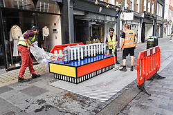 "© Licensed to London News Pictures. 12/09/2019. LONDON, UK.  Workmen begin the installation of ""Walala Lounge"", designed by artist and designer Camille Walala.  South Molton Street in Mayfair will be transformed into an urban living room.  10 sculptural benches, accompanied by planters and a series of oversized flags strung, bunting-style, from shopfront to shopfront, will convert the street into an immersive corridor of colour as part of this year's London Design Festival.  Photo credit: Stephen Chung/LNP"