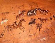 Nineteenth century Navajo pictographs of horses and riders with other animals done in charcoal and paint, shallow cave in Canyon del Muerto, Canyon de Chelly National Monument, Arizona. (CDM-263)