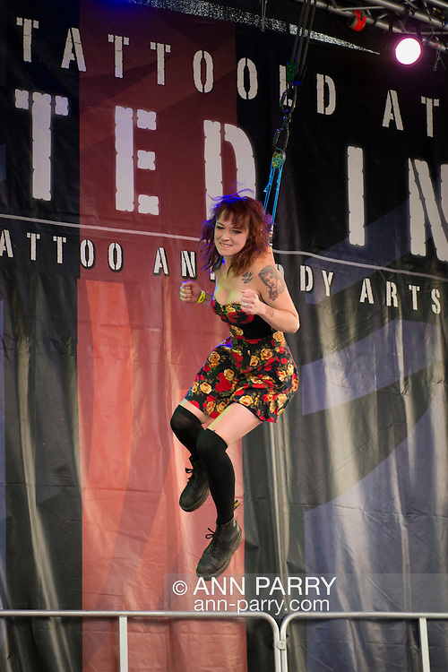Garden City, New York, USA. 14th September 2014. Catalina, a young woman, is suspended from two ropes with hooks pierced through the skin of her back, at an outdoor suspension show at the United Ink Flight 914 tattoo convention at the Cradle of Aviation museum of Long Island.