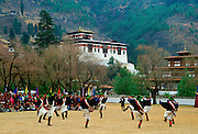 A crowd sit to watch men dressed in traditional costumes dancing as part of a dance festival taking place beside the Paro Dzong a fortress and buddhist monastery, Paro, Bhutan.