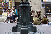 Off duty soldiers and two girls sit and talk on some steps in Ben Yahuda Street, Jerusalem, Israel