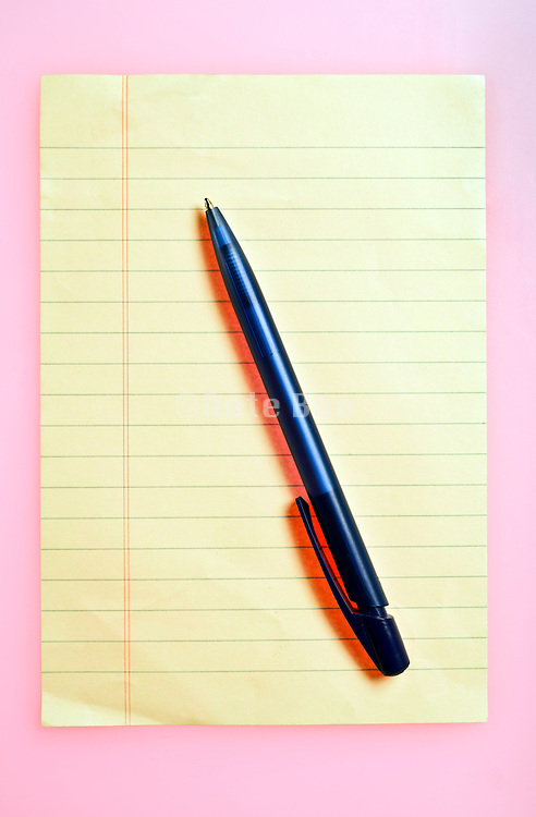 yellow notepad paper with pen