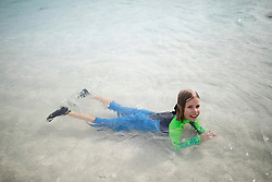 Portrait of girl in wetsuit floating on water, Mauritius