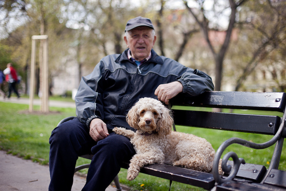 A pensioner is resting with his dog on a bench in front of the main railway station in the Czech capital Prague.