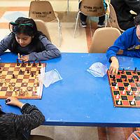 Clockwise from the top left, Khloe Hidalgo, 8, Joel Denetclaw, 7, Elijah Denetclaw, 5, and Sieanna Johnson, 9, play chess, Wednesday, May 22 as part of the Octavia Fellin Public Library Children's Branch Chess Club.