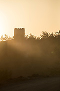Silhouette of old Genoese watchtower backlit by sunset light, Chios, Greece