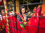 """03 FEBRUARY 2016 - BANGKOK, THAILAND:  A woman shops for Chinese New Year mementos before Chinese New Year in Bangkok. Thailand has the largest overseas Chinese population in the world; about 14 percent of Thais are of Chinese ancestry and some Chinese holidays, especially Chinese New Year, are widely celebrated in Thailand. Chinese New Year, also called Lunar New Year or Tet (in Vietnamese communities) starts Monday February 8. The coming year will be the """"Year of the Monkey.""""            PHOTO BY JACK KURTZ"""