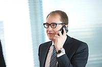 DEU, Deutschland, Germany, Berlin, 12.03.2014: <br />Bundesverkehrsminister Alexander Dobrindt (CSU) telefoniert mit seinem Smartphone (BlackBerry Bold) vor Beginn der 9. Kabinettsitzung im Bundeskanzleramt.