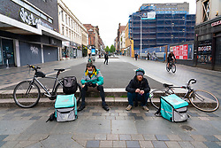 Glasgow, Scotland, UK. 14 May 2020.  With Scotland still in Covid-19 lockdown the city centre of Glasgow remains deserted with with few members of the public on the streets and shops, offices and restaurants closed. Pictured; Deliveroo courier cyclists take a break on Sauchiehall Street. Iain Masterton/Alamy Live News