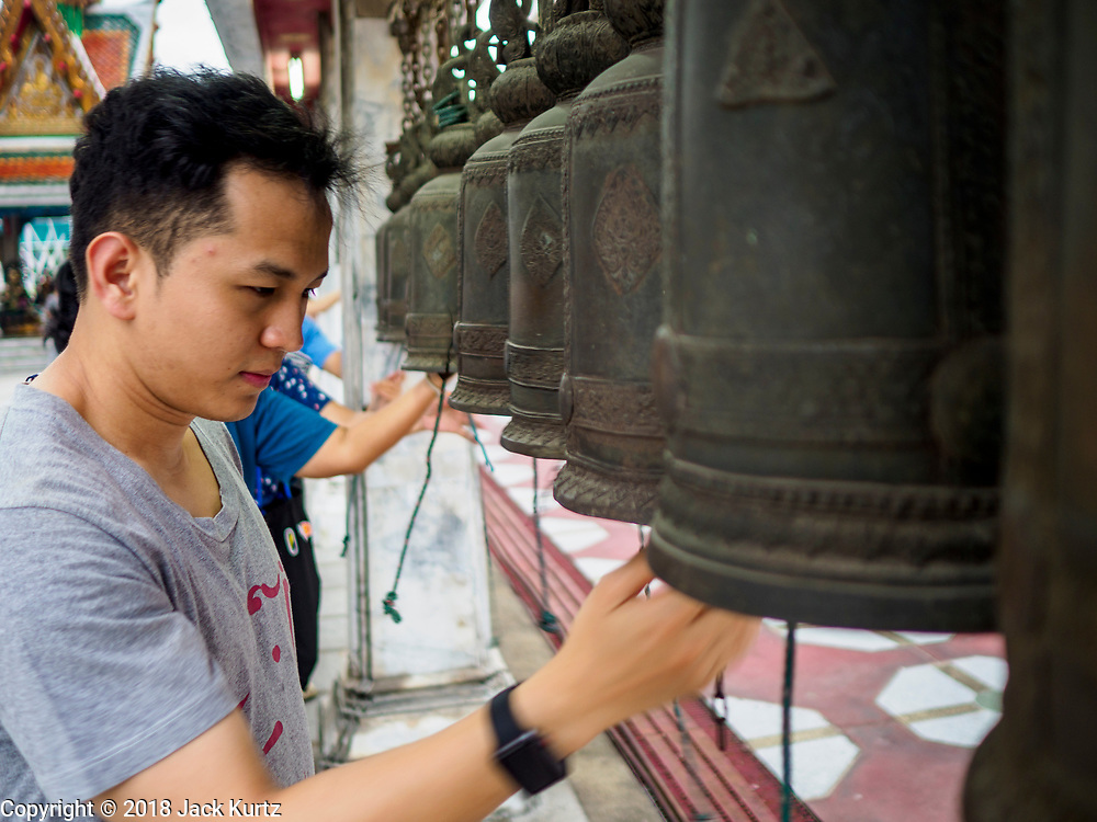 29 MAY 2018 - BANGKOK, THAILAND: A man rings prayer bells to make merit during Vesak observances at Wat Hua Lamphong in Bangkok. Vesak is the Buddha's birthday, and one of the most important holy days in the Theravada Buddhist religion. Many Thais visit their local temples for Vesak and rededicate themselves to the Dharma, listen to talks about Buddhism and make merit by bringing flowers to the temple.        PHOTO BY JACK KURTZ