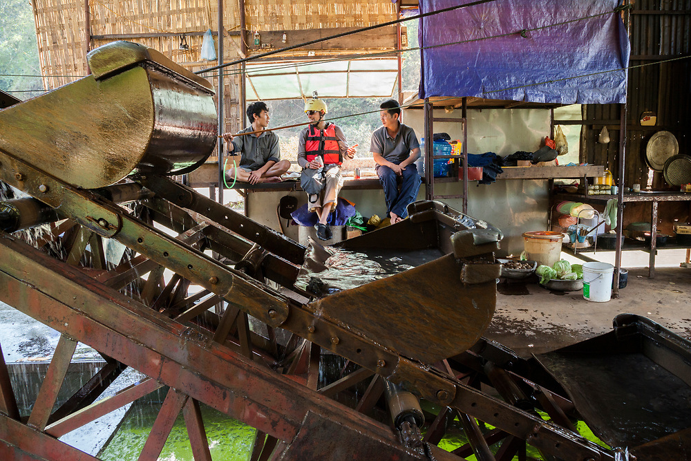Robert Hahn (center) chats with Vietnamese workers, while drinking a Vietnamese beer, on a mechanical gold dredge floating on the Nam Ou River, Laos. Six men live on the vessel for months, rotating throughout the day and working in pairs to keep the machine in constant operation.