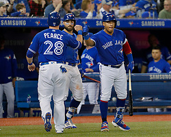 April 29, 2018 - Toronto, ON, U.S. - TORONTO, ON - APRIL 29: Toronto Blue Jays Outfield Steve Pearce (28) is congratulated after crossing home plate and scoring by teammates Infield Yangervis Solarte (26) (R) and Center field Kevin Pillar (11) during the MLB game between the Texas Rangers and the Toronto Blue Jays on April 29, 2018 at Rogers Centre in Toronto, ON. (Photo by Jeff Chevrier/Icon Sportswire) (Credit Image: © Jeff Chevrier/Icon SMI via ZUMA Press)
