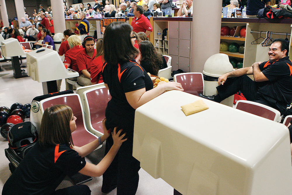 Coach Oscar Garnica laughs during the regional tournament as Megan Weir, 16, left, leaves white handprints on 17-year-old Charlotte Johnson's butt after heavily dusting them with powder from a rosin bag the bowlers use to keep their hands dry. After falling behind to Selah during league play, the Lions were surprised and upset, so all the varsity girls got matching handprints during the break before bakers.