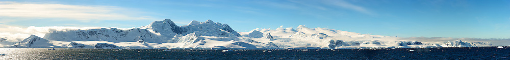 A high resolution panorama of the snow-covered mountains lining the shore of Fournier Bay on the western coast of the Antarctic Peninsula.