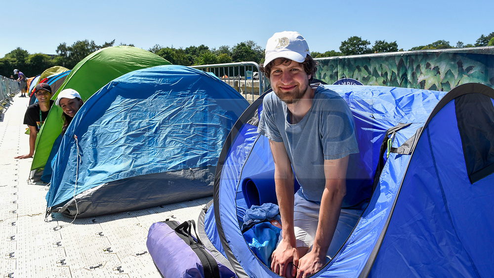 """© Licensed to London News Pictures. 30/06/2018. LONDON, UK.  Darius Platt-Vowles from Gloucestershire poses in his tent in Wimbledon Park.  He is the first in """"The Queue"""" for premium tickets, having arrived on Thursday 28 June, four days before the Wimbledon tennis championships are to begin on 2 July.  He hopes to be able to obtain tickets to centre court to see his idol, Roger Federer.  Behind him are Monique Hefti from Massachusetts (number 2 position) and Stefan Moser from Salzburg (number 3 position). Photo credit: Stephen Chung/LNP"""