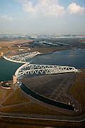 Nederland, Zuid-Holland, Nieuwe Waterweg, 19-09-2009; Functioneringssluiting Maeslantkering: de waterkering in de Nieuwe Waterweg wordt een maal per jaar, voordat het stormseizoen begint, getest. Tijdens  het sluiten van de kering ligt alle scheepvaartverkeer naar de Rotterdamse haven stil. De eigenlijk kering bestaat uit twee (holle) kerende wanden die nadat ze op hun plaats zijn gebracht, afgezonken worden door er water in te pompen. In de voorgond een van de dokken waar de wand normaal gesporken in opgeborgen is. .De Maeslantkering sluit normaal gesproken alleen bij dreigende stromvloed en bij een waterstand van 3 meter of meer boven NAP. De kering, onderdeel van de Deltawerken, vormt samen met de Hartelkering de Europoortkering en beschermt Rotterdam en achterland bij extreme waterstanden. .Netherlands, Hoek van Holland - Rotterdam harbour. Aerial view of the new storm surge barrier (Maeslantkering) in the Nieuwe waterweg during the so-called functioning closure, taking place one a year before the storm season begins. The waterway, leading to the Port of Rotterdam, is closed during the test..luchtfoto (toeslag), aerial photo (additional fee required).foto/photo Siebe Swart