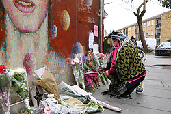 © Licensed to London News Pictures. 10/01/2019. London, UK. A fan places the flower on a mural and shrine to David Bowie in Brixton, on the third anniversary of his death. Photo credit: Dinendra Haria/LNP