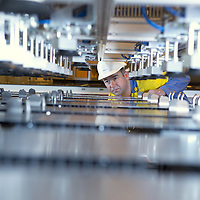 Steel worker with shiny steel plates on HI TECH production line for Auto parts