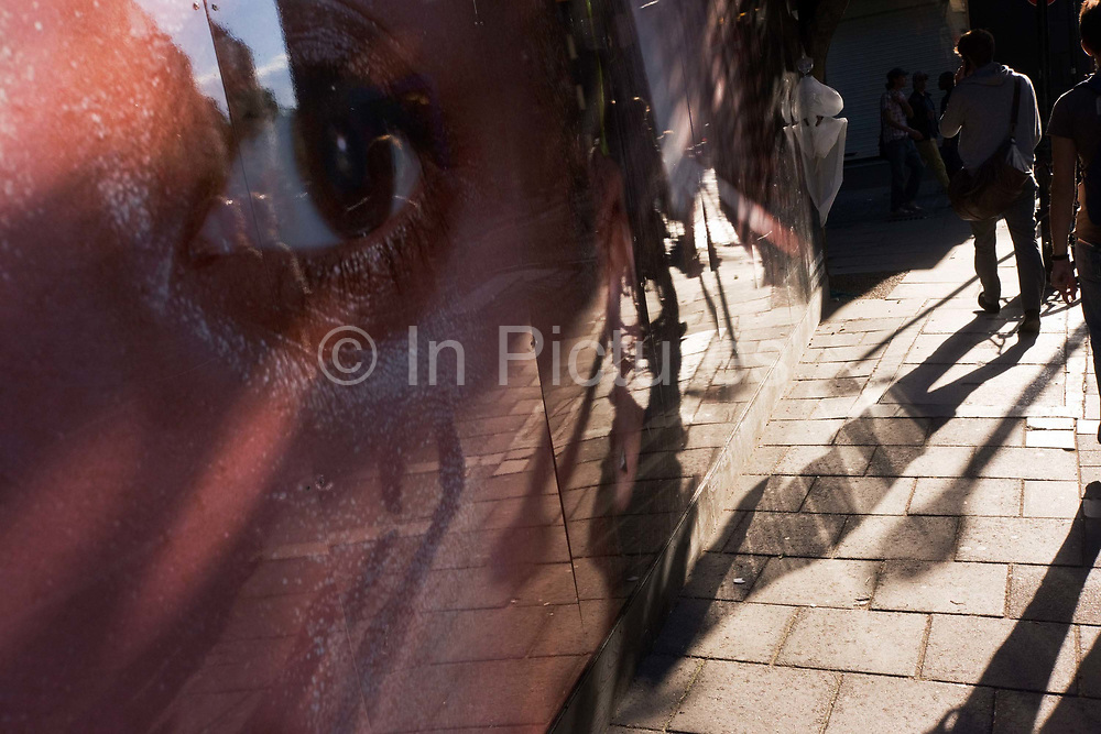 A giant eye from a construction site hoarding appears to be watching pedestrians and their long shadows on Neal Street, London. Reminiscent of an Orwellian 'Big Brother' scenario, where in the book 1984, the State is seen to be spying on its citizens, we see the portion of the large face's eye open and gazing at the passers-by who walk past unaware of their secret surveillance. It is an autumn afternoon and long shadows stretch across the pavement as the pedestrians get on with everyday life - activities that may require reporting on by those needing to know what the People are doing, saying and thinking.