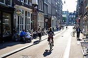 In Amsterdam fietst een meisje op een vouwfiets door de binnenstad waar mensen op een terras genieten van het mooie weer.<br /> <br /> In Amsterdam, a girl on a folding bike cycles downtown where people on a terrace are enjoying the beautiful weather.