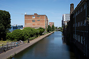 Looking over the towpath of the Birmingham and Fazeley canal in Newtown as the Coronavirus lockdown continues, the city centre is still very quiet while more traffic and people are returning, and with restrictions due to be relaxed further in the coming days, the quiet city may be coming to an end as businesses are set to start to reopen soon on 27th May 2020 in Birmingham, England, United Kingdom. Coronavirus or Covid-19 is a respiratory illness that has not previously been seen in humans. While much or Europe has been placed into lockdown, the UK government has put in place more stringent rules as part of their long term strategy, and in particular social distancing.