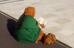 Woman sitting on ground reading at the Golden Temple at Amritsar; Punjab; India,
