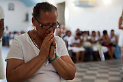 Mixed race middle aged Brazilian woman praying in Church at front of ceremony. Often the lines between Candomble and Catholicism are blurred. This is especially true with the Sao Lazaro event in late January in Salvador, Bahia, Brazil, the city which is known as the home of Candomble. Sao Lazaro represents healing and the sick.