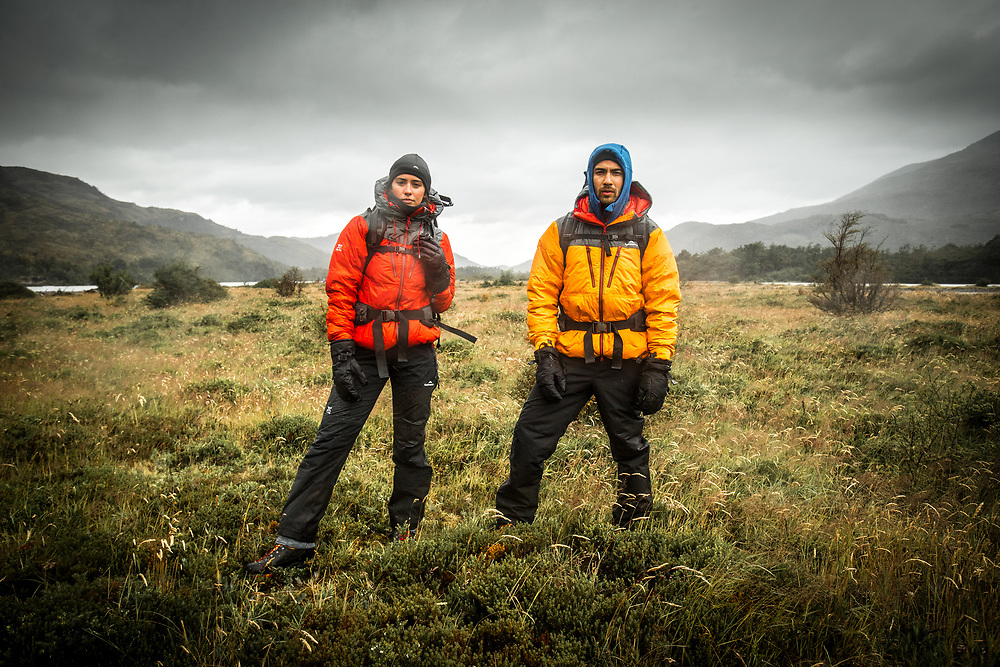 Two adventurers staring into the camera in a remote area with bad weather in Torres del Paine National Park, Chile.