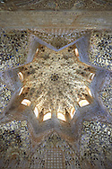 """Arabesque Moorish stalactite or morcabe ceiling in the Hall of the Two Sisters, Palacios Nazaries Alhambra. Granada, Andalusia, Spain. . The Alhambra is a palace and fortress complex located in Granada, Andalusia, Spain. It was originally constructed as a small fortress in 889 CE on the remains of ancient Roman fortifications. The Alhambra was renovated and rebuilt in the mid-13th century by the Arab Nasrid emir Mohammed ben Al-Ahmar of the Emirate of Granada, who built its current Alhambra palace and walls. The Alhambra was converted into a royal palace in 1333 by Yusuf I, Sultan of Granada. The decoration of The Alhambra consists for the upper part of the walls, as a rule, of Arabic inscriptions—mostly poems by Ibn Zamrak and others praising the palace—that are manipulated into geometrical patterns with vegetal background set onto an arabesque setting (""""Ataurique""""). Much of this ornament is carved stucco (plaster) rather than stone. Tile mosaics (""""alicatado"""") of The Alhambra, with complicated mathematical patterns (""""tracería"""", most precisely """"lacería""""), are largely used as panelling for the lower part. .<br /> <br /> Visit our SPAIN HISTORIC PLACXES PHOTO COLLECTIONS for more photos to download or buy as wall art prints https://funkystock.photoshelter.com/gallery-collection/Pictures-Images-of-Spain-Spanish-Historical-Archaeology-Sites-Museum-Antiquities/C0000EUVhLC3Nbgw <br /> .<br /> Visit our ISLAMIC HISTORICAL PLACES PHOTO COLLECTIONS for more photos to download or buy as wall art prints https://funkystock.photoshelter.com/gallery-collection/Islam-Islamic-Historic-Places-Architecture-Pictures-Images-of/C0000n7SGOHt9XWI"""