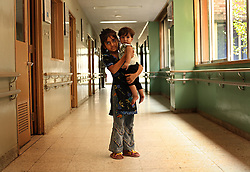 Haram Naz, 7, holds nine-month-old Mezab Rahmat in the hallway of Children's Hospital at the Pakistan Institute of Medical Sciences in Islamabad, Pakistan, Sept. 19, 2007.