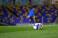 Footballs on pitch with AFC Wimbledon goalkeeper Nikola Tzanev (13) warming up prior to kick off in background during the EFL Trophy match between AFC Wimbledon and U21 Arsenal at Plough Lane, London, United Kingdom on 8 December 2020.