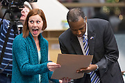 A mother of a young patient reacts as retired Neurosurgeon and Republican presidential candidate Dr. Ben Carson signs her son's card during a visit to the MUSC Children's Hospital December 22, 2015 in Charleston, South Carolina. Carson stopped by to listen to Christmas carols and greet the young patients.