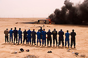 """Firefighters from the Kuwait Oil Company (called KWWK: Kuwait Wild Well Killers) pray at noon by the first oil well fire they were working on in Iraq's Rumaila Oil field. Later in the day they extinguished this smoky fire and the next day stopped the flow of gas and oil with drilling mud using what is called a """"stinger"""", (a tapered pipe on the end of a long steel boom controlled by a bulldozer. Drilling mud, under high pressure, is pumped through the stinger into the well, stopping the flow of oil and gas). The Rumaila field is one of Iraq's biggest oil fields with five billion barrels in reserve. The burning wells in the Rumaila Field were ignited by retreating Iraqi troops when the US and UK invasion began in March 2003. Rumaila is also spelled Rumeilah."""