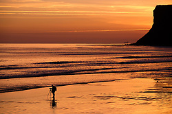 © Licensed to London News Pictures. <br /> 26/03/20167. <br /> Saltburn by the Sea, UK.  <br /> <br /> A photographer stands on the beach taking pictures as a spectacular sunrise starts the day over the beach in Saltburn by the Sea.<br /> <br /> Photo credit: Ian Forsyth/LNP