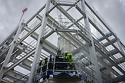 Construction workers fix lights to a building site Christmas tree in central London.