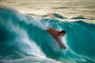 Boogie boarder catches a wave on the Kona Coast at White Sands Beach, Kailua-Kona, North Kona District, Big Island, Hawaii