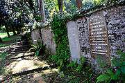Gravestones from the original and predominantly Christian cemetery are inlaid into a; brick wall. Fort Canning Green; Singapore