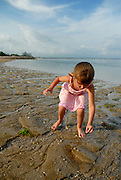 Australian tourist child (5 years old) picking pebbles up from beach. Sanur, Bali, Indonesia.