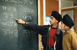 Two secondary school pupils standing in classroom pointing at blackboard,